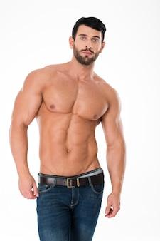 Портрет красивого спортивного мужчины с обнаженным торсом, стоящего изолированно на белой стене