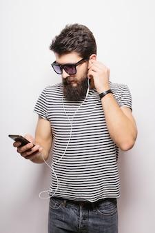 白い壁に隔離された携帯電話を保持しているイヤホンを持つハンサムな魅力的なひげを生やした男の肖像画