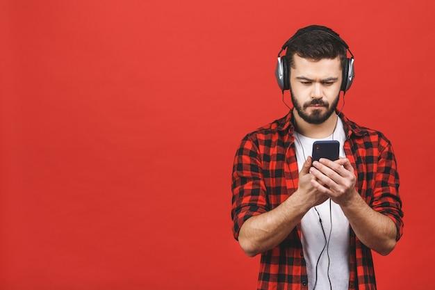 Портрет красивого привлекательного бородатого человека при наушники держа мобильный телефон изолированный.