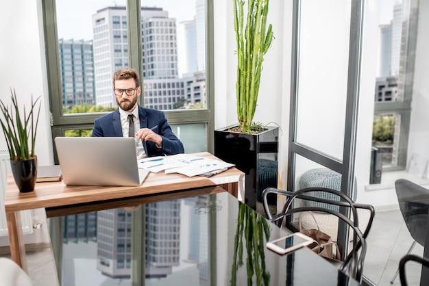 고층 빌딩의 아름다운 전망을 감상할 수 있는 고급 사무실 내부에 앉아 노트북으로 일하는 잘생긴 은행원의 초상화