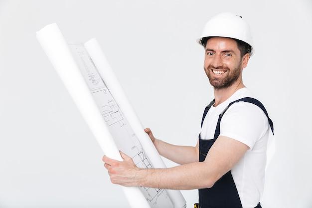 Портрет красивого бородатого строителя в комбинезоне, стоящего изолированно над белой стеной и смотрящего на проект