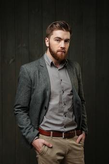 Портрет красивого бородатого мужчины в повседневном костюме, стоящего с руками в карманах, изолированного на черном деревянном фоне