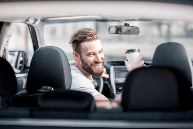 一杯のコーヒーと車の前部座席に座って振り返るハンサムなひげを生やした男の肖像画