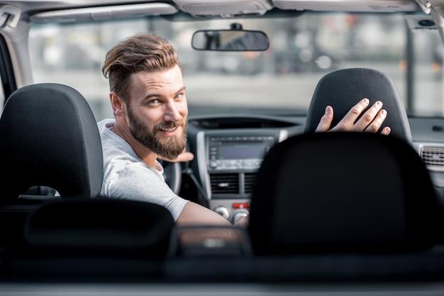 차 앞 좌석에 앉아 뒤를 돌아보고 있는 잘생긴 수염 난 남자의 초상화