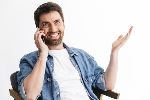 白い壁に隔離された椅子に座って、携帯電話で話しているカジュアルな服を着ているハンサムなひげを生やした男の肖像画