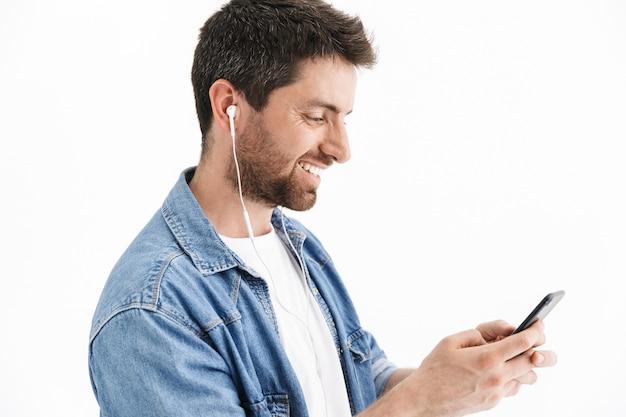 Портрет красивого бородатого мужчины в повседневной одежде, стоящего изолированно, слушая музыку в наушниках и держащего мобильный телефон