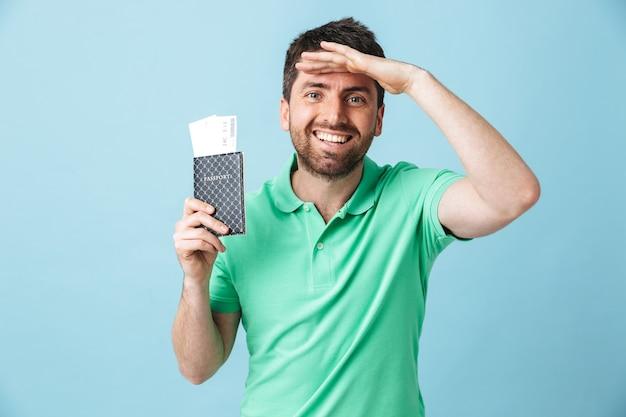 Портрет красивого бородатого мужчины в повседневной одежде, стоящего изолированно над синей стеной, показывая паспорт с билетами на самолет, празднуя