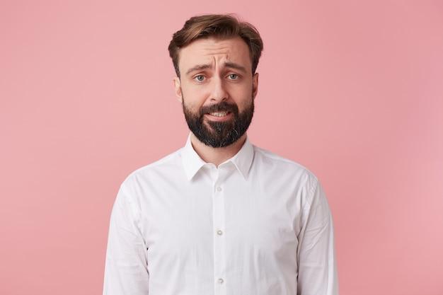 방금 카드 집을 파괴 한 후회하는 잘 생긴 수염 난 남자의 초상화. 찡그림과 카메라 격리 분홍색 배경을 찾고.