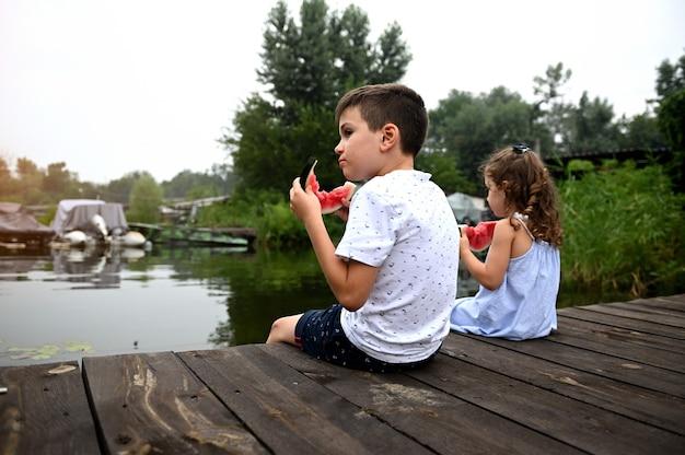 スイカを食べて、日没で美しい夏の日を楽しんで、彼の妹の隣の桟橋に座って、美しい自然を賞賛するハンサムな男の子の肖像画。田舎の夏休み