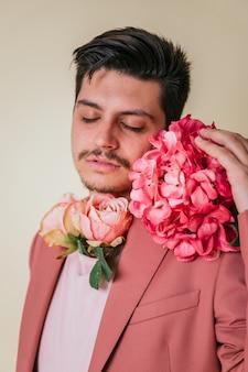 目を閉じてハンサムな男の子の肖像画。ピンクのスーツを着て、首と顔の横に花を持つハンサムな若い男