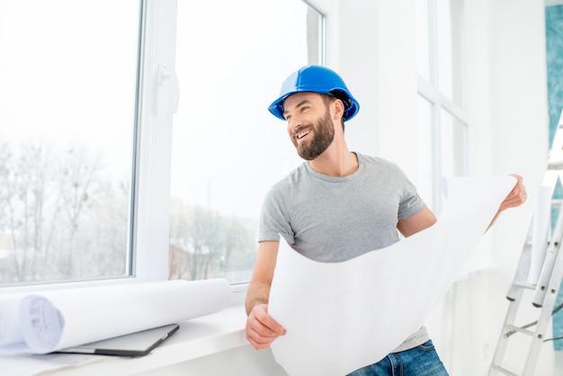 Портрет красивого строителя, прораба или ремонтника в каске, смотрящего на бумажные рисунки у окна в помещении