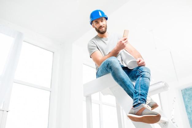 白いインテリアのはしごに図面と一緒に座っているヘルメットのハンサムなビルダー、職長または修理工の肖像画
