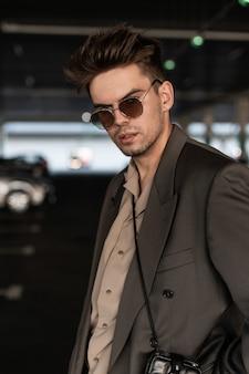 ファッショナブルな灰色のスーツに無精ひげを持つハンサムなビジネスマンの男の肖像画は、都会の背景にサングラスを通して見えます