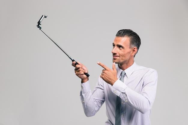 分離された自撮り棒を保持しているハンサムなビジネスマンの肖像画