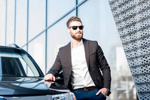 Портрет красивого бизнесмена в солнцезащитных очках, стоящего возле автомобиля на открытом воздухе перед фасадом современного здания