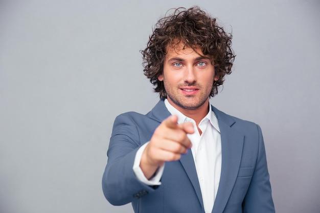 Портрет красивого бизнесмена, указывая пальцем на переднюю по серой стене