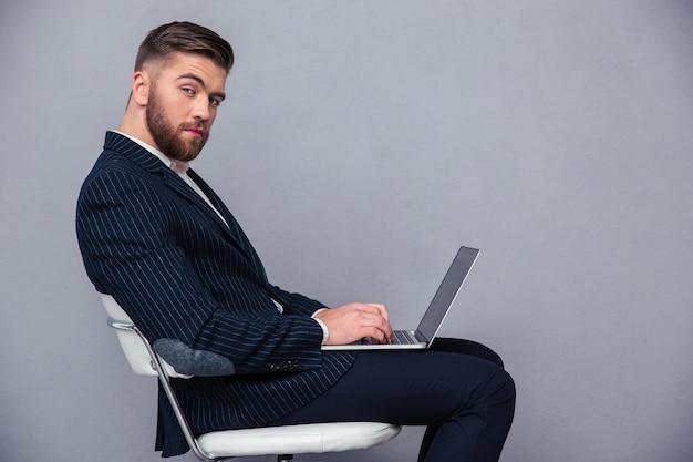 Портрет красивого бизнесмена, сидящего на офисном стуле с ноутбуком и смотрящего в камеру над серой стеной