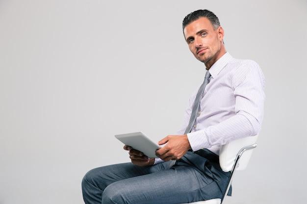 分離されたタブレット コンピューターでオフィスの椅子に座っているハンサムなビジネスマンの肖像画