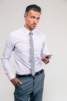 Портрет красивого бизнесмена с помощью смартфона изолированы