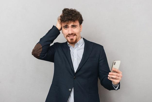 Портрет красивого растерянного недовольного молодого бизнесмена изолированного над серой стеной с помощью мобильного телефона.