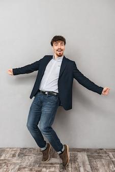 Портрет красивого эмоционального молодого делового человека, изолированного над серой стеной, танцы.