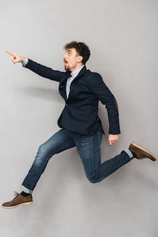 Портрет красивого эмоционального молодого делового человека, изолированного над серой стеной, прыгающей указывая.
