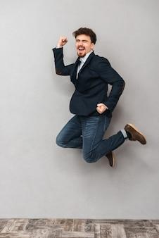 Портрет красивого эмоционального молодого делового человека, изолированного над серой стеной, прыгающей.
