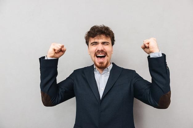 Портрет красивого возбужденного молодого делового человека, изолированного над серой стеной, делает жест победителя.