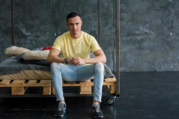 Портрет красивого модного молодого человека в желтой футболке и джинсах на чердаке