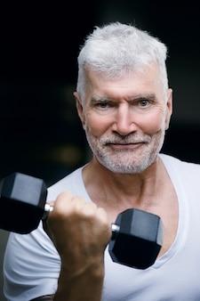 ダンベルを持つハンサムな白髪の年配の男性の肖像画。スポーツとヘルスケアの概念