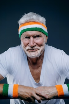 スポーツのヘッドバンドを持つハンサムな白髪の年配の男性の肖像画。スポーツとヘルスケアの概念