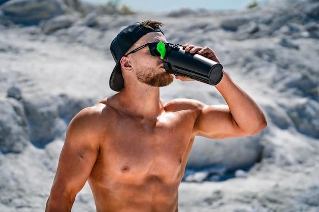 Портрет красивого полуголого культуриста в очках и кепке с бутылкой воды.