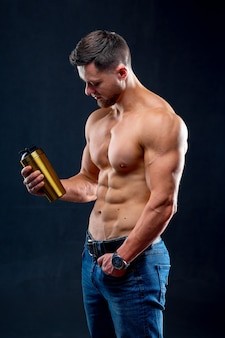 Портрет красивого полуголого культуриста со спортивной бутылкой воды. человек позирует на темном фоне.