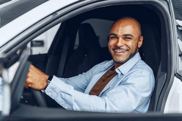 彼の新しく購入した車に座っているハンサムな幸せなアフリカ系アメリカ人の男の肖像画