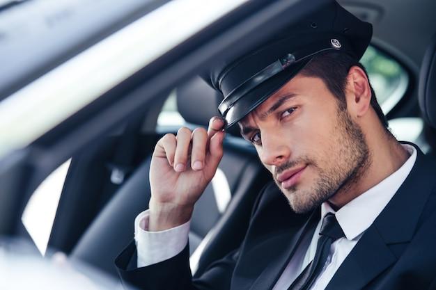 차에 앉아 경례 제스처를 만드는 잘 생긴 남성 운전사의 초상화