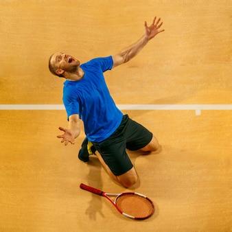 コートの壁で彼の成功を祝うハンサムな男性テニスプレーヤーの肖像画。人間の感情、勝者、スポーツ、勝利の概念