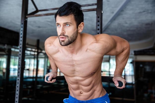 Портрет красивого мужчины, делающего упражнения на брусьях в фитнес-зале
