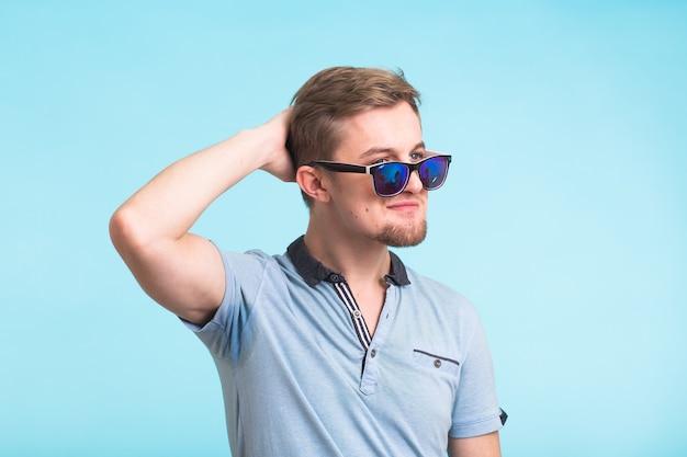 Портрет красивого мужчины, одетого в футболку поло на синем