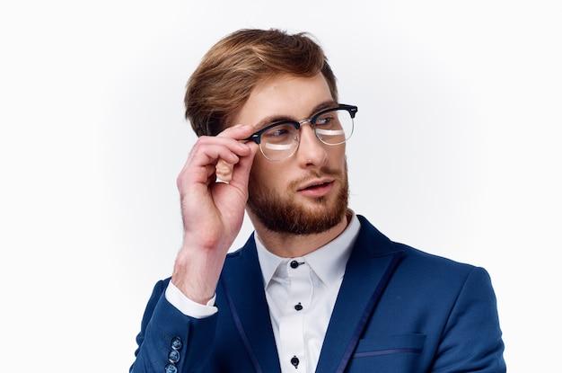 眼鏡と明るい背景の上の古典的なスーツを着たハンサムな男の肖像画。高品質の写真