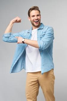 Портрет красивого мужчины в джинсовой рубашке, показывающий его бицепс со согнутой рукой