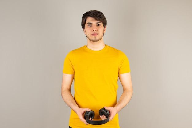 Портрет красивой модели человека в желтой рубашке с наушниками.