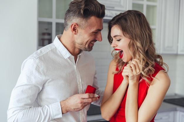 彼の幸せなガールフレンドを提案しているハンサムな男の肖像