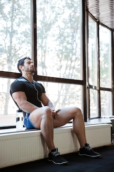 피트니스 체육관에서 쉬고 잘 생긴 남자의 초상화