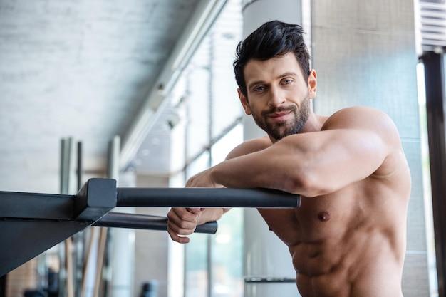 Портрет красивого мужчины, отдыхающего возле брусьев в фитнес-зале