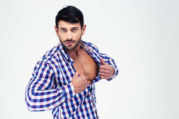 Портрет красивого мужчины, расстегивающего рубашку, изолированного на белой стене