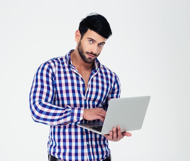 Портрет красивого мужчины, использующего портативный компьютер, изолированного на белой стене и смотрящего на фронт