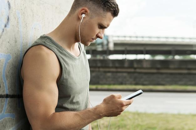 イヤホンでハンサムな男の肖像画。路上でのフィットネストレーニング中に音楽を聴く。