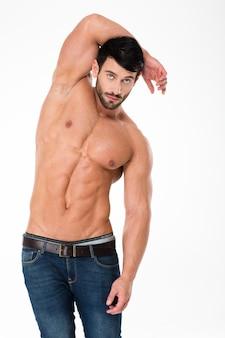 Портрет красивого мужчины с мускулистым телом, позирующего изолированным на белой стене и смотрящим вперед
