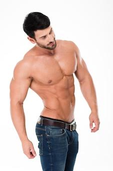 Портрет красивого мужчины с мускулистым телом, позирующего изолированно на белой стене и смотрящего в сторону