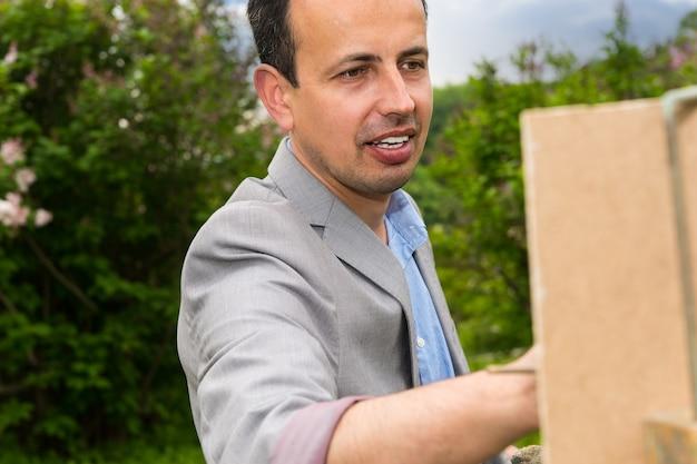 미술 수업 중 가대와 이젤 그림에 잘 생긴 중년 쾌활한 남성 예술가의 초상화